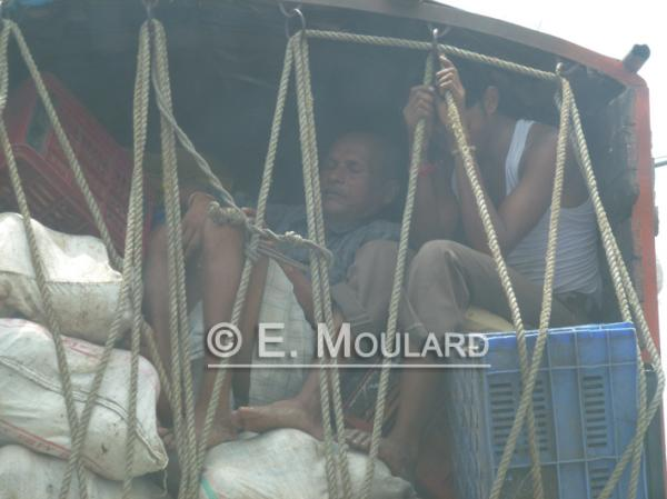 In a trucks, bags, crates and people
